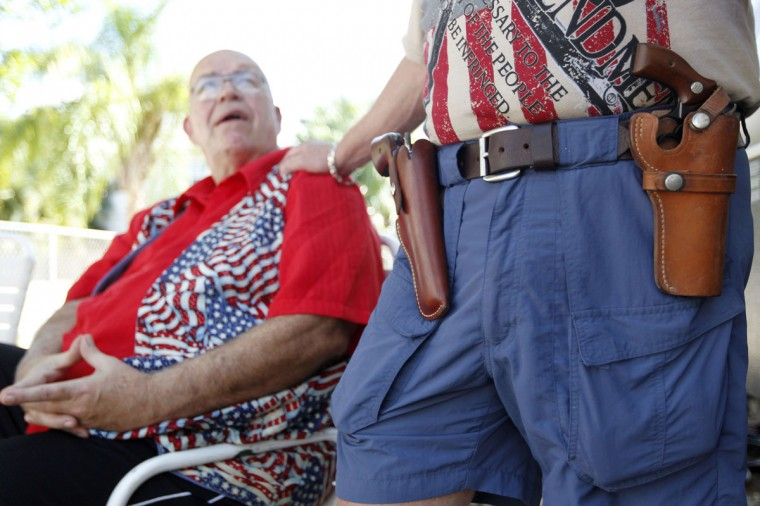 Huie Gordon, a retired Monroe County Sheriff's Deputy and neighbor of Doug Varrieur (wearing his twin revolvers) chat in the yard of Varrieur's home in Big Pine Key in the Florida Keys March 5, 2014. Varrieur, 57, discovered a little-noticed part of Florida law which prohibits local governments from restricting gun rights in any way, and in December he set up a personal gun range on his property in a residential subdivision. Neighbors were outraged by the live gunfire, but their surprise was nothing compared to that of municipal leaders, who were shocked to realize there was nothing they could do about it. Picture taken March 5, 2014. (REUTERS/Andrew Innerarity)