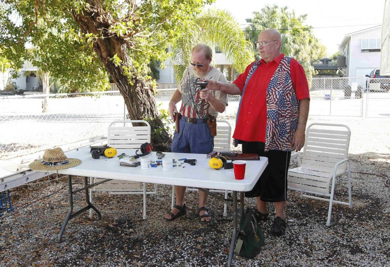 Doug Varrieur (L) and Huie Gordon, his friend, neighbor and retired Monroe County Sheriff's Deputy prepare to practice their firing stances with unloaded weapons in the yard of Varrieur's home in Big Pine Keys in the Florida Keys March 5, 2014. Varrieur, 57, discovered a little-noticed part of Florida law which prohibits local governments from restricting gun rights in any way, and in December he set up a personal gun range on his property in a residential subdivision. Neighbors were outraged by the live gunfire, but their surprise was nothing compared to that of municipal leaders, who were shocked to realize there was nothing they could do about it. Picture taken March 5, 2014. (REUTERS/Andrew Innerarity)