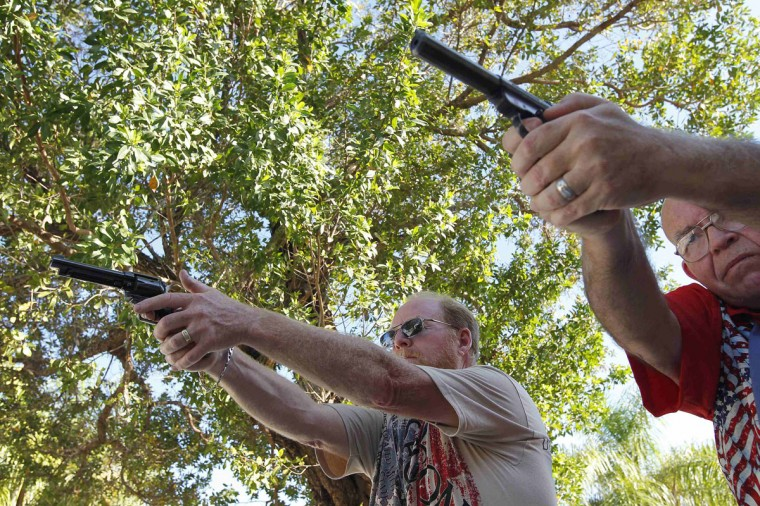 Doug Varrieur (L) and Huie Gordon, his friend, neighbor and retired Monroe County Sheriff's Deputy practice their firing stance with unloaded weapons in the yard of Varrieur's home in Big Pine Keys in the Florida Keys March 5, 2014. Varrieur, 57, discovered a little-noticed part of Florida law which prohibits local governments from restricting gun rights in any way, and in December he set up a personal gun range on his property in a residential subdivision. Neighbors were outraged by the live gunfire, but their surprise was nothing compared to that of municipal leaders, who were shocked to realize there was nothing they could do about it. Picture taken March 5, 2014. (REUTERS/Andrew Innerarity)