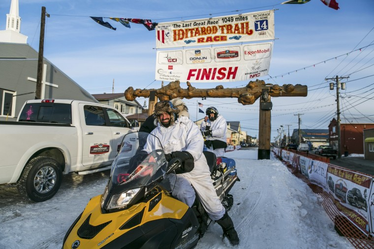 Snow mobilers who led the way during the night exit the Iditarod trail on Front Street during the Iditarod dog sled race in Nome, Alaska, March 11, 2014. The nearly 1,000-mile (1,600-km) Iditarod Trail Sled Dog Race commemorates a 1925 rescue mission that carried diphtheria serum by sled-dog relay to the coastal community of Nome, which remains the final destination in this 42nd edition of the event. (REUTERS/Nathaniel Wilder)