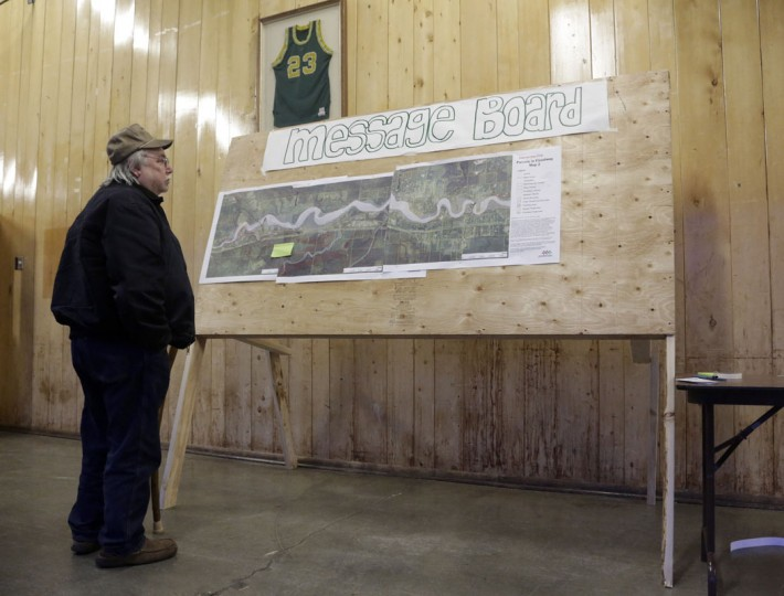 Longtime resident Lewis Cope inspects an aerial photo of areas that were affected by the landslide after a rain-soaked hillside collapsed on Saturday at the Community Center in Darrington, Washington March 25, 2014. The likely death toll from a devastating weekend landslide in Washington state rose to 24 on Tuesday after rescue workers recovered two bodies and believed they had located eight more, the local fire chief said. (Jason Redmond/Reuters)