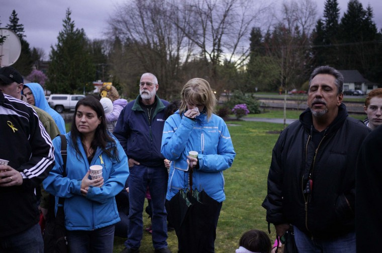 A woman cries during the singing of Amazing Grace at a candlelight vigil for mudslide victims in Arlington, Washington March 25, 2014. The likely death toll from a devastating weekend landslide in Washington state rose to 24 on Tuesday after rescue workers recovered two bodies and believed they had located eight more, the local fire chief said. (Rick Wilking/Reuters)