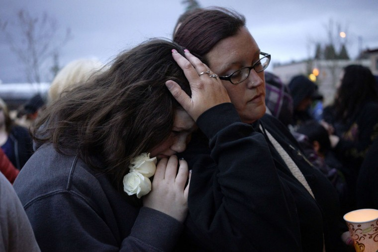 Sarah Halstead (R) comforts her daughter Allison at a candlelight vigil for mudslide victims in Arlington, Washington March 25, 2014. The likely death toll from a devastating weekend landslide in Washington state rose to 24 on Tuesday after rescue workers recovered two bodies and believed they had located eight more, the local fire chief said. (Rick Wilking/Reuters)
