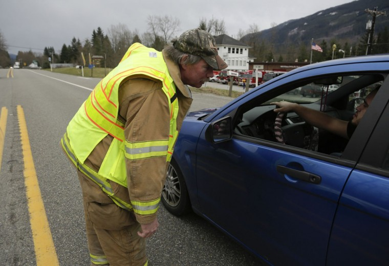An emergency worker instructs vehicles to turn around after a large mudslide blocked Highway 530 near Oso, Washington, March 22, 2014. Three people died and at least eight others were injured on Saturday in a landslide that destroyed six or more homes along a state highway in northwest Washington state, officials said. (Jason Redmond/Reuters)