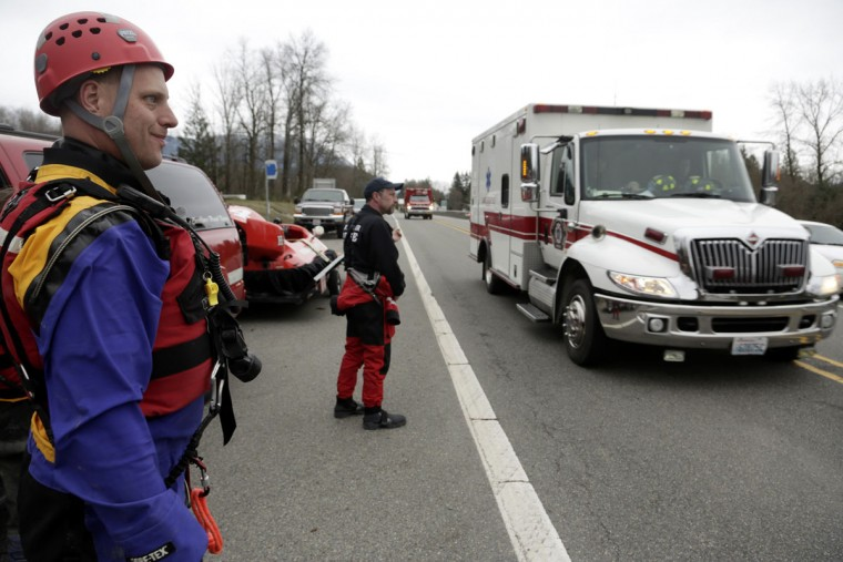 Members of a swift water rescue team look on as an ambulance drives past after a large mudslide blocked Highway 530 near Oso, Washington, March 22, 2014. Three people died and at least eight others were injured on Saturday in a landslide that destroyed six or more homes along a state highway in northwest Washington state, officials said. (Jason Redmond/Reuters)