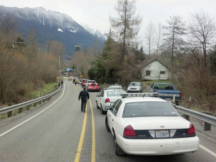 Officials and cars line the highway at the site of a large mudslide in this handout photo provided by the Washington State Police near Oso, Washington, March 22, 2014. (Washington State Police/Handout via Reuters)