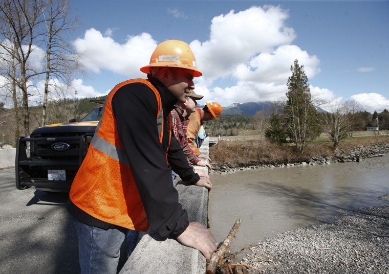 Workers observe the Stillaguamish River near the area where a landslide blocks Highway 530 near Oso, Washington, March 23, 2014. (Lindsey Wasson/Pool/Reuters)