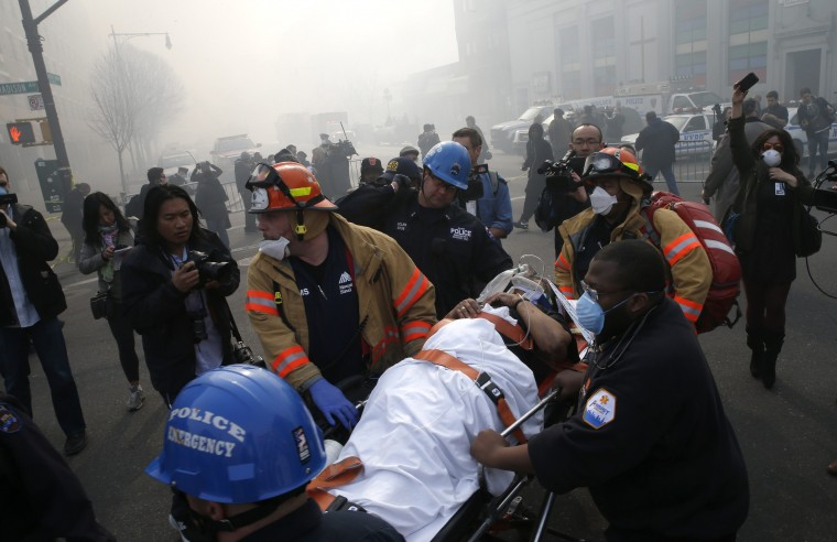 A victim is evacuated by emergency personal near an apparent building explosion fire and collapse in the Harlem section of New York City, March 12, 2014. A building collapsed in a largely residential block of Upper Manhattan on Wednesday and the New York City Fire Department was searching for anyone trapped in the debris, officials said. (REUTERS/Mike Segar)