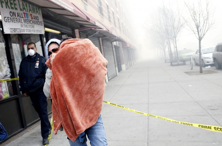 A man carries a child wrapped in a blanket on East 116th street away from an apparent building explosion fire and collapse in the Harlem section of New York City, March 12, 2014. A building collapsed in a largely residential block of Upper Manhattan on Wednesday and the New York City Fire Department was searching for anyone trapped in the debris, officials said. (REUTERS/Mike Segar)