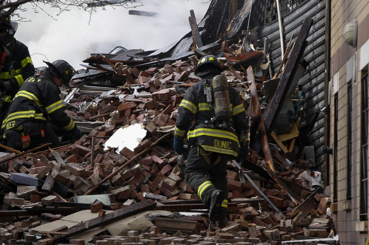 Firefighters go through debris and rubble at the site of a building collapse and fire in Harlem, New York, March 12, 2014. A building collapsed in a largely residential block of Upper Manhattan on Wednesday and the New York City Fire Department was searching for anyone trapped in the debris, officials said. Television images showed heavy smoke and dust rising from the structure at East 114th Street and Park Avenue in East Harlem, which reportedly collapsed at about 9 a.m. (1300 GMT). (REUTERS/Shannon Stapleton)