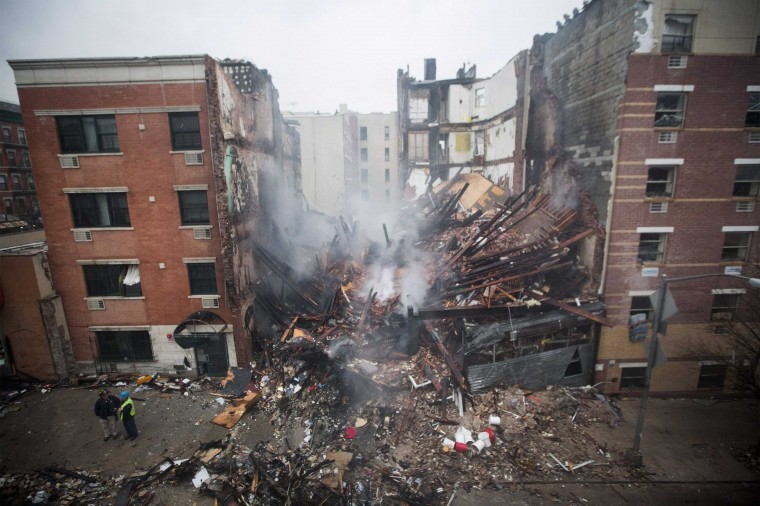 New York City firefighters work at the site of a building explosion and collapse in the Harlem section of New York, March 12, 2014. Two New York City buildings collapsed on Wednesday in an explosion believed to be caused by a gas leak, killing two people, injuring at least 36, and setting off a search for more victims feared trapped in the rubble, officials said. (REUTERS/Brendan McDermid)