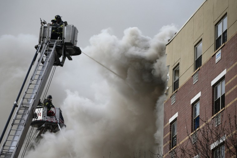 Firefighters try to extinguish a fire at the site of a building collapse in Harlem, New York, March 12, 2014. A building collapsed in a largely residential block of Upper Manhattan on Wednesday and the New York City Fire Department was searching for anyone trapped in the debris, officials said. Television images showed heavy smoke and dust rising from the structure at East 114th Street and Park Avenue in East Harlem, which reportedly collapsed at about 9 a.m. (1300 GMT). (REUTERS/Shannon Stapleton)