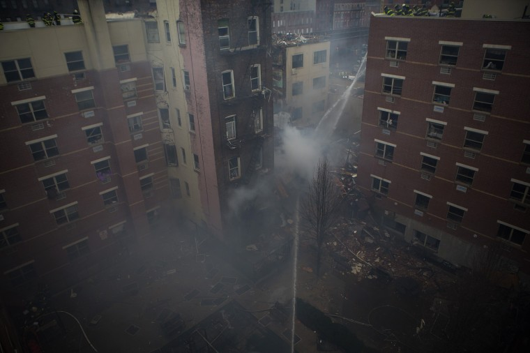 New York City firefighters spray water onto the rubble at an apparent building explosion and collapse in the Harlem section of New York, March 12, 2014. Two New York buildings collapsed on Wednesday in an explosion believed to be caused by a gas leak, killing two people, injuring at least 22, and setting off a search for more feared trapped in the debris, officials said. (REUTERS/Eric Thayer)