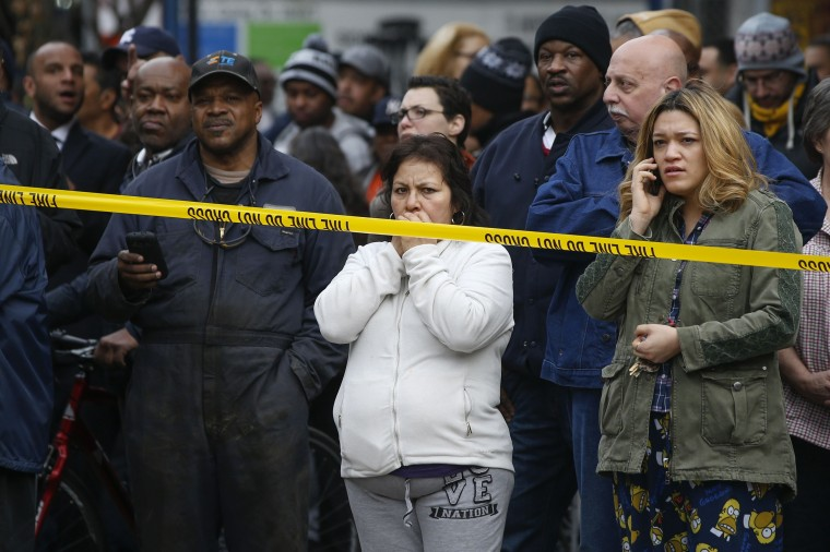 Residents watch from the side lines of a building collapse in Harlem, New York, March 12, 2014. A building collapsed in a largely residential block of Upper Manhattan on Wednesday and the New York City Fire Department was searching for anyone trapped in the debris, officials said. Television images showed heavy smoke and dust rising from the structure at East 114th Street and Park Avenue in East Harlem, which reportedly collapsed at about 9 a.m. (1300 GMT). (REUTERS/Shannon Stapleton)