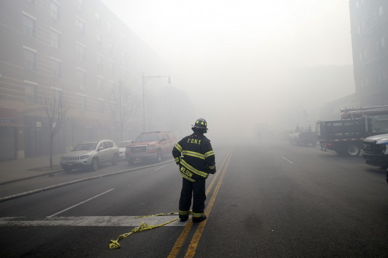 A firefighter stands in smoke filled East 116th street near an apparent building explosion fire and collapse in the Harlem section of New York City, March 12, 2014. A building collapsed in a largely residential block of Upper Manhattan on Wednesday and the New York City Fire Department was searching for anyone trapped in the debris, officials said. (REUTERS/Mike Segar)