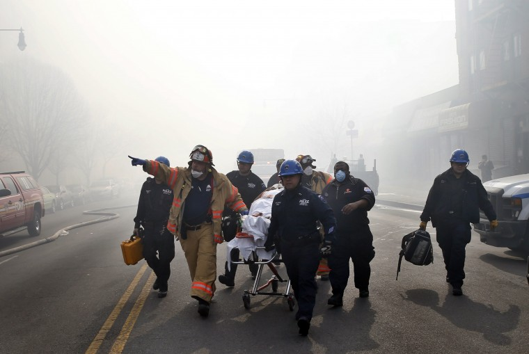A victim is evacuated by emergency personal near an apparent building explosion fire and collapse in the Harlem section of New York City, March 12, 2014. A building collapsed in Upper Manhattan on Wednesday, killing at least one person and injuring more than a dozen, setting off a search for anyone trapped in the debris, officials said. (REUTERS/Mike Segar)