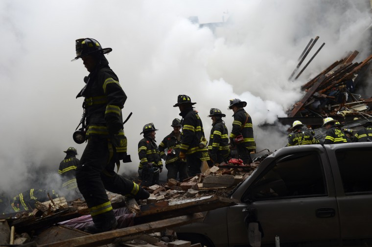 Firemen stand in the rubble at an apparent building explosion fire and collapse in the Harlem section of New York, in this picture provided by the New York City Mayor's Office March 12, 2014. Two New York buildings collapsed on Wednesday in an explosion believed to be caused by a gas leak, killing two people, injuring at least 22, and setting off a search for more feared trapped in the debris, officials said. (REUTERS/Rob Bennett/New York City Mayor's Office/Handout)