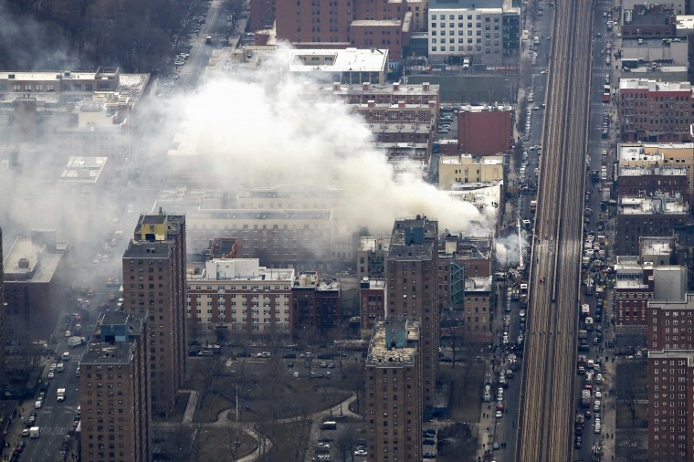 Smoke billows from the site of a building collapse as debris litters railway tracks in this aerial photograph taken over Harlem, New York on March 12, 2014. Two New York buildings collapsed on Wednesday in an explosion believed to be caused by a gas leak, killing two people, injuring at least 22, and setting off a search for more feared trapped in the debris, officials said. During the morning commute, trains were stopped in nearby stations because of debris on the tracks and passengers were ordered off the Metro-North Railroad cars at the Fordham stop in the Bronx, passengers said. (REUTERS/Mike Isler/NYonAir)