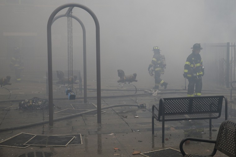 Firefighters walk though smoke at the site of a building collapse in Harlem, New York March 12, 2014. Two New York buildings collapsed on Wednesday in an explosion believed to be caused by a gas leak, killing two people, injuring at least 22, and setting off a search for more feared trapped in the debris, officials said. (REUTERS/Shannon Stapleton)