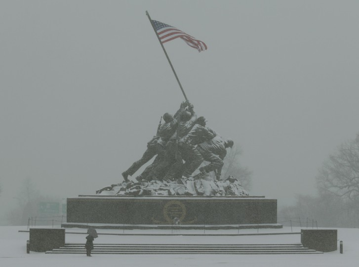 Jeannette Ibrahim (L) photographs the U.S. Marine Corps War Memorial during blizzard conditions in Arlington, Virginia during a snow storm in the Washington metro area March 3, 2014. A powerful winter storm hit the U.S. East Coast on Monday with freezing rain, snow and arctic cold, forcing cancellation of about 2,250 flights, shutting down Washington and closing schools and local governments. (Gary Cameron/Reuters)
