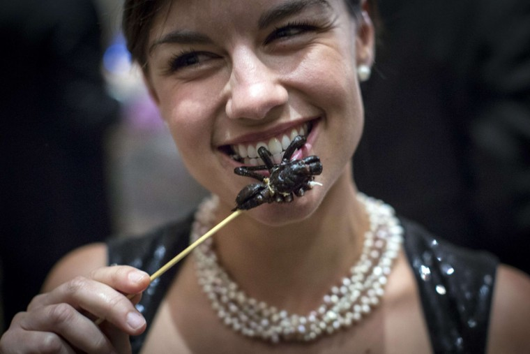 Daniela Kittinger chews a cooked tarantula at the 110th Explorers Club Annual Dinner at the Waldorf Astoria in New York. (Andrew Kelly/Reuters)