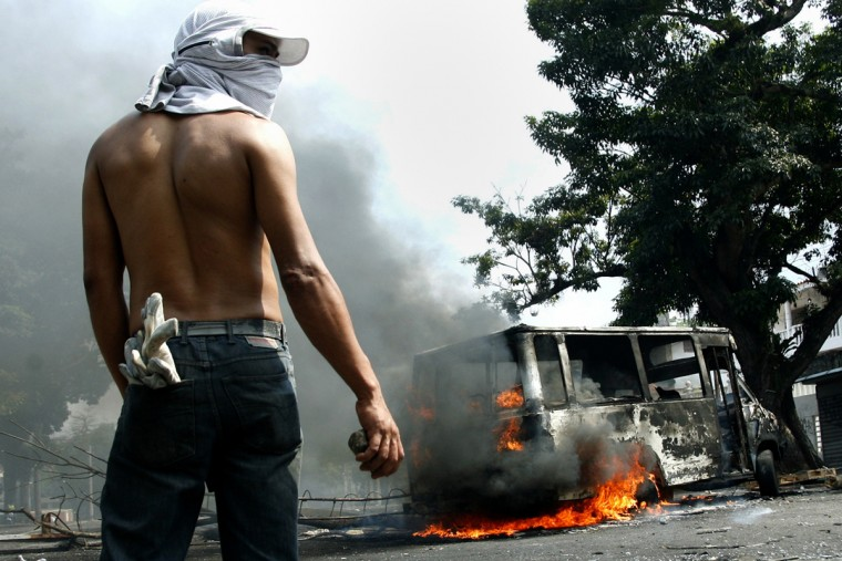 An anti-government protester holds a stone in front of a burning bus during a protest against Nicolas Maduro's government in San Cristobal March 17, 2014. Since early February, students and hardline opposition leaders have been calling supporters onto the streets to protest against Maduro and his socialist government. (Carlos Eduardo Ramirez/Reuters)