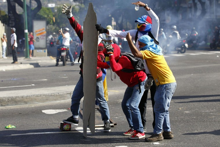 Anti-government protesters take cover from the police behind makeshift shields in Caracas, Venezuela, March 22, 2014. (Carlos Garcia Rawlins/Reuters)