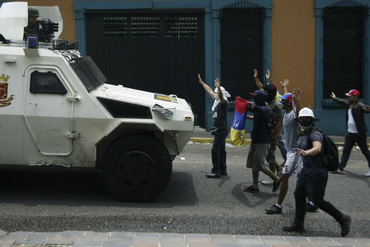 Anti-government protesters stand in front of a National Guard armored vehicle during a protest against Venzuelan President Nicolas Maduro's government in San Cristobal, March 22, 2014. (Carlos Eduardo Ramirez/Reuters)