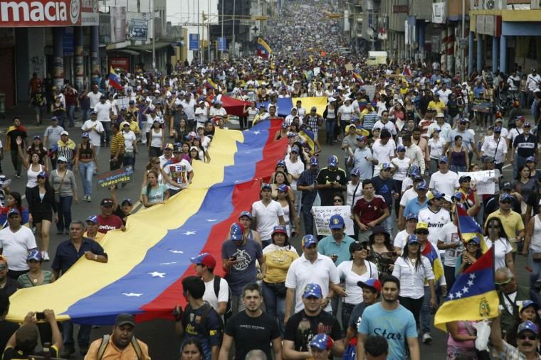 Opposition supporters hold a national a flag during a rally against Venezuelan President Nicolas Maduro's government in San Cristobal, March 22, 2014. (Carlos Eduardo Ramirez/Reuters)