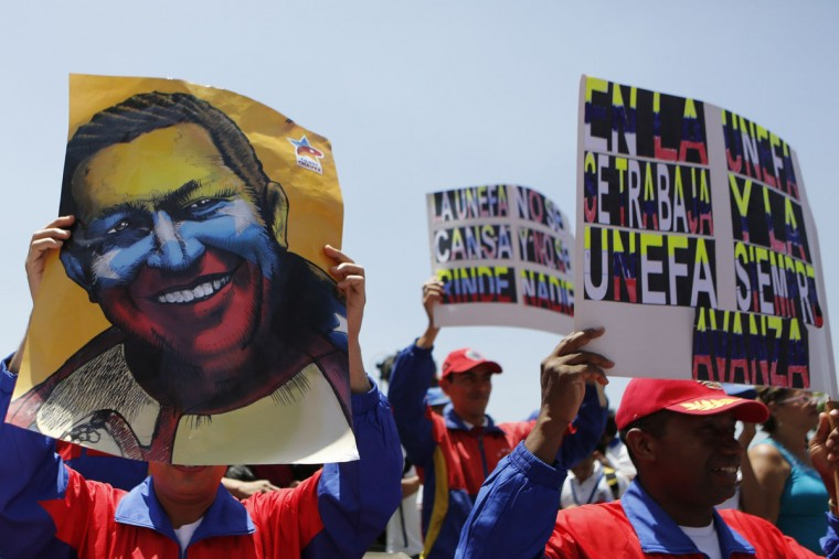 Demonstrators hold a poster of late Venezuelan President Hugo Chavez during a rally to show their support for Venezuela's President Nicolas Maduro's government in Caracas, March 22, 2014. Two Venezuelans died from gunshot wounds during protests against Maduro, witnesses and local media said on Saturday. (Marco Bello/Reuters)