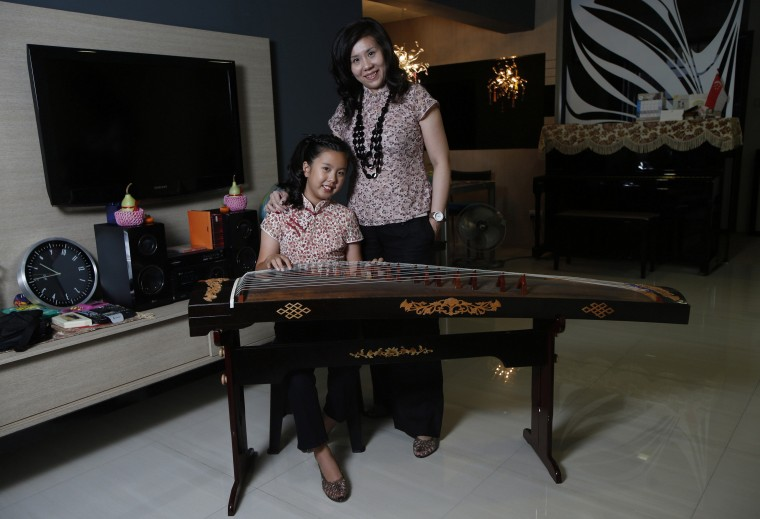 Samann Loh, 40, and her daughter Given Tan, 10, pose for a photograph in their apartment in Singapore February 25, 2014. Samann works as a human resource director at a preschool education group. As a child she had many ambitions, including being a fashion designer and an air stewardess. She later realised her dream of becoming an air stewardess. Samann hopes her daughter can pursue something that she is truly passionate about. Given Tan would like to be a fashion designer when she is older. On March 8 activists around the globe celebrate International Women's Day, which dates back to the beginning of the 20th century and has been observed by the United Nations since 1975. The UN writes that it is an occasion to commemorate achievements in women's rights and to call for further change. Picture taken February 25, 2014. (REUTERS/Edgar Su)
