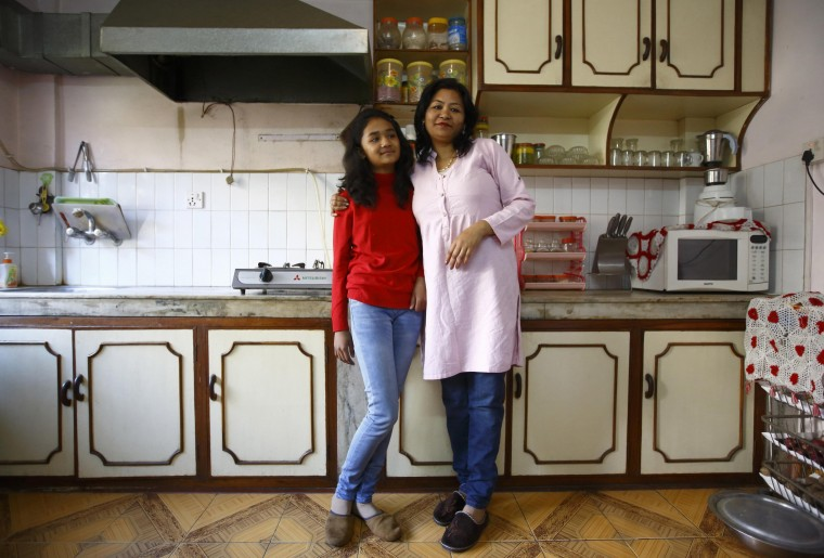 Mohanna Khanal, 35, and her daughter Vipassna Khanal, 12, pose for a photograph in the kitchen of their apartment in Kathmandu February 4, 2014. Mohanna is a school teacher who finished her education when she was 20 years old. Mohanna says that when she was a child, she wanted to become a flight attendant. She hopes that her daughter will become a renowned media personality. Vipassna says that she will finish her education in 2025 and she wants to become a travel agent to promote tourism in Nepal. On March 8 activists around the globe celebrate International Women's Day, which dates back to the beginning of the 20th century and has been observed by the United Nations since 1975. The UN writes that it is an occasion to commemorate achievements in women's rights and to call for further change. Picture taken February 4, 2014. (REUTERS/Navesh Chitraka)