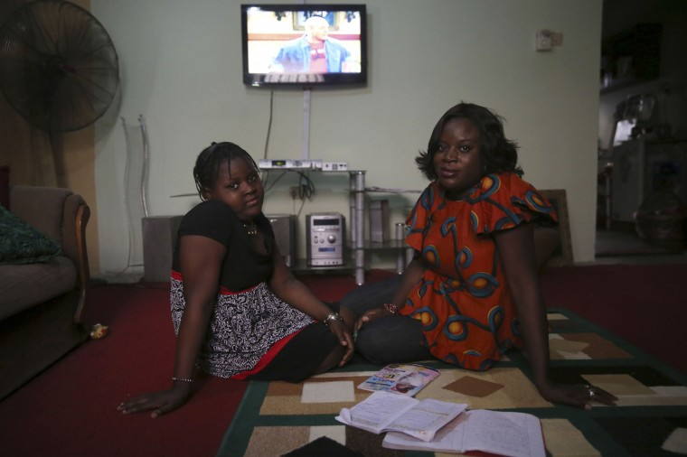 Adetola Ibitoye, 39, sits with her daughter Iteoluwa Ibitoye, 9, in their home in Omole district, Lagos February 16, 2014. When Adetola was growing up, she wanted to run a fashion business. Now she is a clothes designer. Adetola says she wants her daughter to be the best at whatever she sets her mind to be. Her daughter Iteoluwa says she wants to grow up to be a university teacher. On March 8 activists around the globe celebrate International Women's Day, which dates back to the beginning of the 20th century and has been observed by the United Nations since 1975. The UN writes that it is an occasion to commemorate achievements in women's rights and to call for further change. Picture taken February 16, 2014. (REUTERS/Akintunde Akinleye)