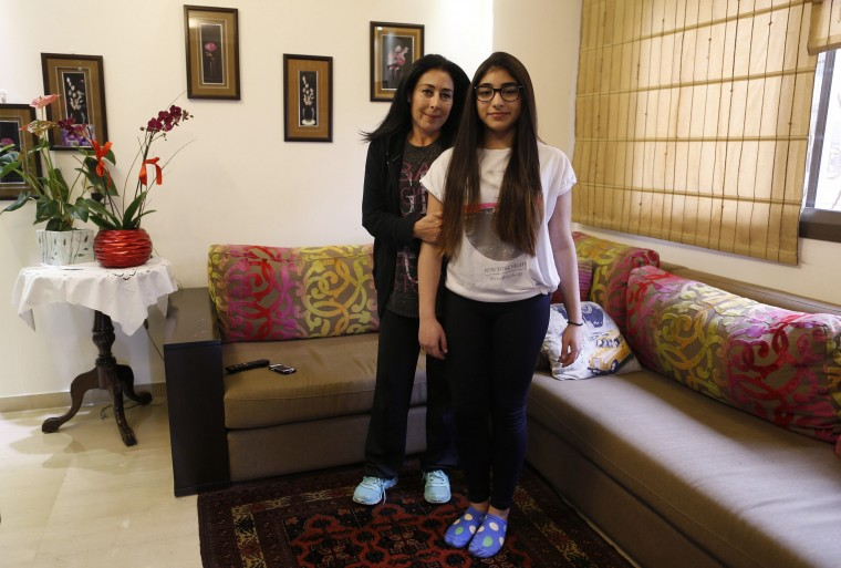Rima Bader, 44, poses with her daughter Reina, 13, inside their apartment in Beirut February 25, 2014. Rima is an interior designer but she says that when she was growing up she wanted to be an engineer. Rima wants her daughter to work in whatever profession she chooses, but she says she would love to see her in the field of engineering. Reina says she will finish education when she is around 21 years old. She wants to be an architect when she grows up. On March 8 activists around the globe celebrate International Women's Day, which dates back to the beginning of the 20th century and has been observed by the United Nations since 1975. The UN writes that it is an occasion to commemorate achievements in women's rights and to call for further change. Picture taken February 25, 2014. (REUTERS/Jamal Saidi)