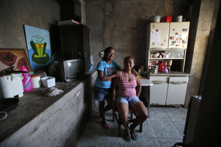 Raimunda Eliandra Alves, 45, poses for a photograph with her daughter Ana Paula Leonardo Justino, 10, at their home at the Pavao-Pavaozinho slum in Rio de Janeiro February 10, 2014. Raimunda is a supermarket cashier who finished her education at age 19. When she was a child, she wanted to become a math teacher when she grew up. She hopes that her daughter Ana Paula will become a veterinarian. Ana Paula says that she will go to high school and then finish college in 2025. She wants to be a vet when she grows up. On March 8 activists around the globe celebrate International Women's Day, which dates back to the beginning of the 20th century and has been observed by the United Nations since 1975. The UN writes that it is an occasion to commemorate achievements in women's rights and to call for further change. Picture taken February 10, 2014. (REUTERS/Sergio Moraes)