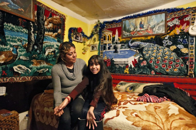 Niculina Fieraru, 39, poses with her daughter Flori Gabriela Dumitrache, 13, in their room in Gura Sutii village, Romania February 25, 2014. Niculina Fieraru is unemplo