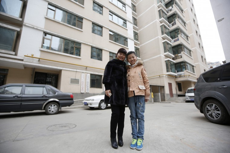 Zhang Haijing, 41, and her daughter Zhu Nuo, 11, pose for a photograph outside their apartment building in Lanzhou, Gansu province February 5, 2014. Zhang Haijing finished her education at age 23 and is a mid-level manager for Xinhua Bookstore Group. When she was a child, she wanted to become a pre-school teacher. Zhang Haijing says she wants her daughter Zhu Nuo to have a stable job, but does not mind what she does so long as she is happy. Zhu Nuo says she wants to get a doctoral degree and become a professor. On March 8 activists around the globe celebrate International Women's Day, which dates back to the beginning of the 20th century and has been observed by the United Nations since 1975. The UN writes that it is an occasion to commemorate achievements in women's rights and to call for further change. Picture taken February 5, 2014. (REUTERS/Aly Song)