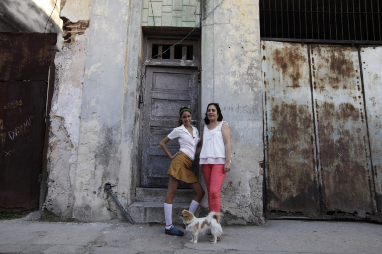 Damaris Matos Curbelo, 43, and her daughter Ana Laura Villar Matos, 14, pose for a photograph outside their home in central Havana February 12, 2014. Damaris finished her education at age 21 and works as a secretary in the office of the Historian of the City of Havana. Damaris says that when she was a child she wanted to become a doctor, and that she hopes her daughter will become a doctor. Her daughter Ana Laura says she would like to be a biologist. On March 8 activists around the globe celebrate International Women's Day, which dates back to the beginning of the 20th century and has been observed by the United Nations since 1975. The UN writes that it is an occasion to commemorate achievements in women's rights and to call for further change. Picture taken February 12, 2014. (REUTERS/Enrique De La Osa)