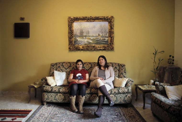 Hala Tanmus, 40, and her daughter Maya, 10, pose for a picture in the living room of their home in the West Bank city of Ramallah February 18, 2014. Hala is a secretary who finished her education at age 20. When she was younger she wanted to become a lawyer. She hopes that her daughter Maya will become an interior designer. Maya, who says she will finish education age 20, would also like to become an interior designer. On March 8 activists around the globe celebrate International Women's Day, which dates back to the beginning of the 20th century and has been observed by the United Nations since 1975. The UN writes that it is an occasion to commemorate achievements in women's rights and to call for further change. Picture taken February 18, 2014. (REUTERS/Ammar Awad)