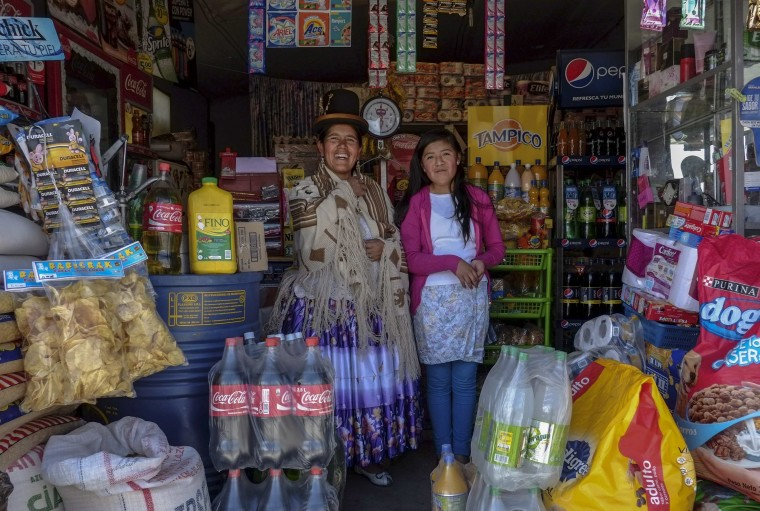 Lucia Mayta, 43, and her daughter Luz Cecilia, 12, pose for a photograph inside their bodega in La Paz February 24, 2014. Lucia studied until the fourth grade of primary school, and knows how to read and write and do basic math. Lucia runs a bodega, and the family live in a back room. She hopes to build a house in the future. Luz Cecilia is in seventh grade and wants to be a singer. On March 8 activists around the globe celebrate International Women's Day, which dates back to the beginning of the 20th century and has been observed by the United Nations since 1975. The UN writes that it is an occasion to commemorate achievements in women's rights and to call for further change. Picture taken February 24, 2014. (REUTERS/David Mercado)