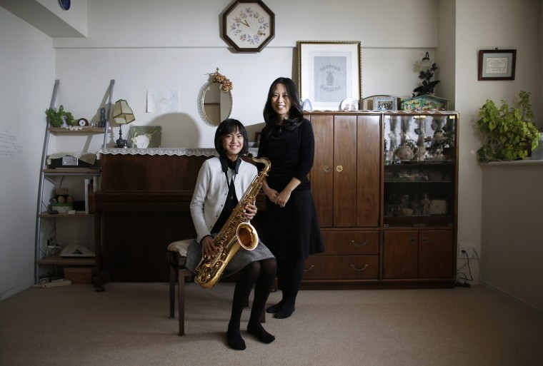 Manami Miyazaki (R), 39, and her daughter Nanaha, 13 and holding her alto saxophone, pose for a photograph at their home in Tokyo February 3, 2014. Manami, who is a housewife, studied until she was 20. Her ambition was to work somewhere where she could meet lots of people. She hopes that her daughter will build a loving home with a happy marriage. She says it would be great if her daughter could find work that makes use of her abilities and interests. Nanaha wants to be either a designer, musician or a nurse. On March 8 activists around the globe celebrate International Women's Day, which dates back to the beginning of the 20th century and has been observed by the United Nations since 1975. The UN writes that it is an occasion to commemorate achievements in women's rights and to call for further change. Picture taken February 3, 2014. (REUTERS/Toru Hanai)