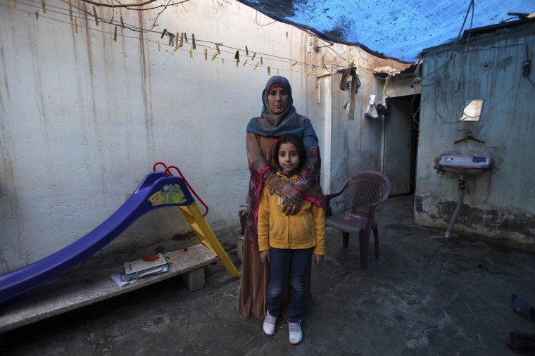 Bidaa Mhem Thabet al-Hasan (Um Suleiman), 39, poses with her daughter Mariam Khaled Masto, 9, outside their home in Deir al-Zor, Syria February 23, 2014. Bidaa is the director of a school founded by a group of teachers and volunteers. Her ambition was to become a gynaecologist. She hopes that her daughter will join the pharmacy school, but says that she will let her follow her own ambitions and that her success will make her happy. Mariam will finish her education in 13 years. She would like to become an Arabic teacher in Deir al-Zor. On March 8 activists around the globe celebrate International Women's Day, which dates back to the beginning of the 20th century and has been observed by the United Nations since 1975. The UN writes that it is an occasion to commemorate achievements in women's rights and to call for further change. Picture taken February 23, 2014. (REUTERS/Khalil Ashawi)