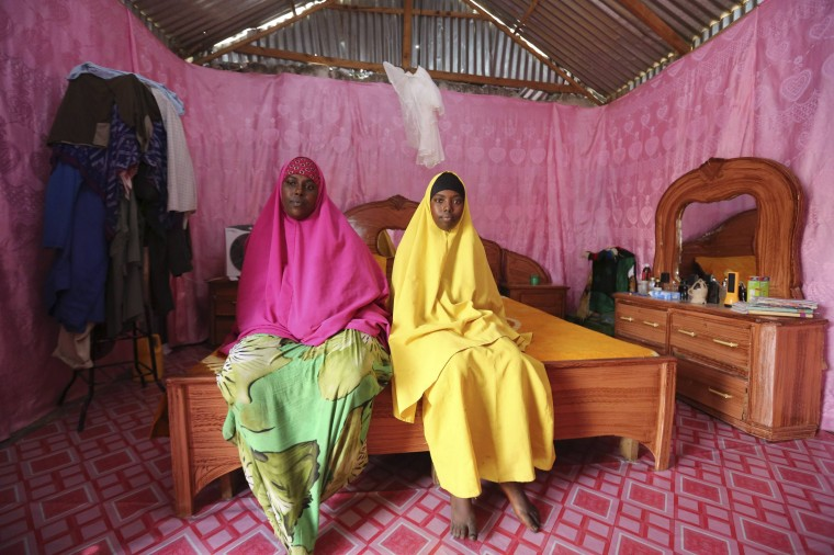 Saciido Sheik Yacquub, 34, poses for a picture with her daughter Faadumo Subeer Mohamed, 13, at their home in Hodan district IDP camp in Mogadishu February 11, 2014. Saciido, who runs a small business, wanted to be a business woman when she was a child. She studied until she was 20. She hopes that Faadumo will become a doctor. Faadumo will finish school in 2017 and hopes to be a doctor when she grows up. On March 8 activists around the globe celebrate International Women's Day, which dates back to the beginning of the 20th century and has been observed by the United Nations since 1975. The UN writes that it is an occasion to commemorate achievements in women's rights and to call for further change. Picture taken February 11, 2014. (REUTERS/Feisal Omar )