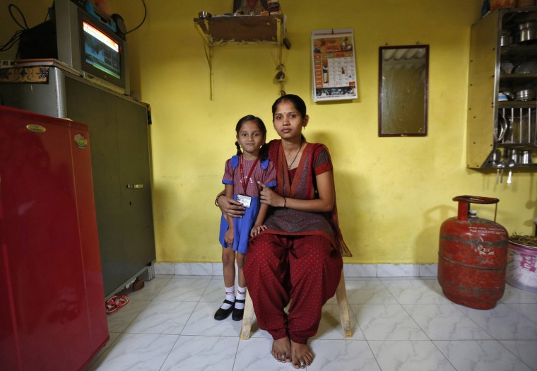 Sulochna Mohan Sawant, 23, poses with her five-year-old daughter Shamika Sawant inside their home in Mumbai February 13, 2014. Sulochna, who works as a maid, wanted to become a doctor when she was a child. However, she could only study until the age of 14. Sulochna wants her daughter to become a teacher, Shamika also wants to become a teacher. On March 8 activists around the globe celebrate International Women's Day, which dates back to the beginning of the 20th century and has been observed by the United Nations since 1975. The UN writes that it is an occasion to commemorate achievements in women's rights and to call for further change. Picture taken February 13, 2014. (REUTERS/Mansi Thapliyal)