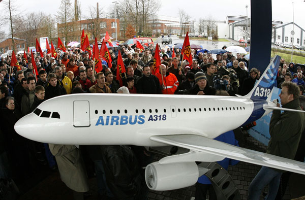 Employees protest beside a model of an Airbus A318 at the Airbus facility in the northern German town of Nordenham. (REUTERS/Christian Charisius)