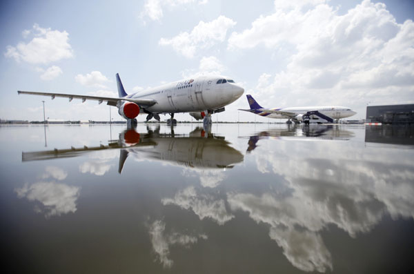 Thai Airways Airbus A300 aircrafts are parked on the flooded tarmac at Don Muang airport in Bangkok on October 26, 2011. (REUTERS/Bazuki Muhammad)