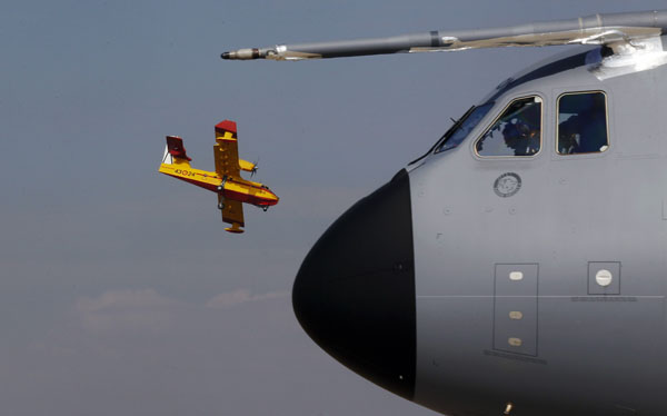 A Canadair CL-215 plane lands beside a prototype of an A400M Airbus military plane at Torrejon de Ardoz military base near Madrid on March 1, 2012. (REUTERS/Andrea Comas)