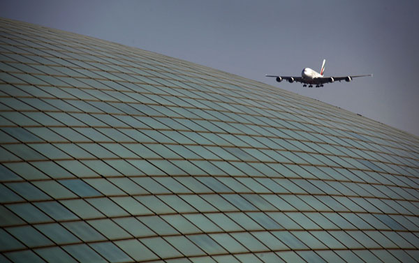 An Emirates airlines Airbus A380 comes in for landing over the roof of the Beijing Capital International Airport's train station on March 6, 2012. (REUTERS/David Gray)
