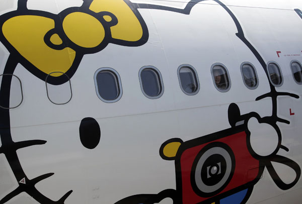 A passenger looks out of an Airbus A330-300 aircraft of Taiwan's Eva Airlines, decorated with Hello Kitty motifs, in Taoyuan International Airport, northern Taiwan, on April 30, 2012. (REUTERS/Pichi Chuang)