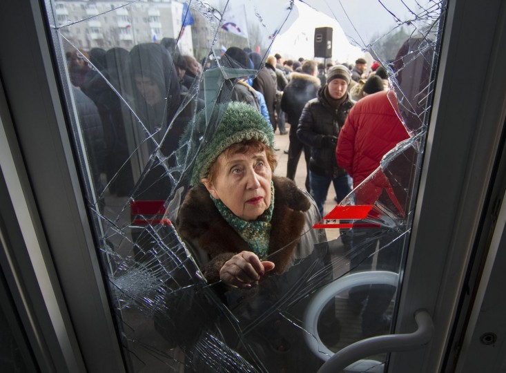 A woman looks through a damaged entrance door as pro-Russian demonstrators hold a rally outside the regional government building in Donetsk on March 3, 2014. (Reuters photo)